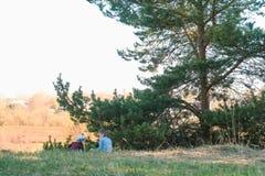 Il fratello e la sorella giocano insieme nell'erba nella foresta Fotografie Stock