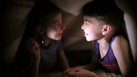 Il fratello e la sorella hanno letto un libro sotto una coperta con una torcia elettrica in una stanza scura alla notte I bambini stock footage