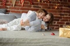 Il fratello e la sorella hanno messo sulla lotta allegra sul grande letto Immagine Stock