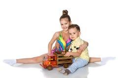 Il fratello e la sorella stanno giocando con un'automobile del giocattolo Immagine Stock Libera da Diritti