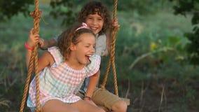 Il fratello e la sorella stanno imbrogliando intorno, stanno ridendo e giurando su un'oscillazione Vacanze estive nel villaggio archivi video