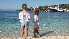Il fratello e la sorella, studenti gettano l'acqua di mare blu delle pietre in chiaro sui precedenti della città croata e del mar video d archivio