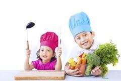 Il fratello e la sorella cucinano la verdura Immagini Stock Libere da Diritti