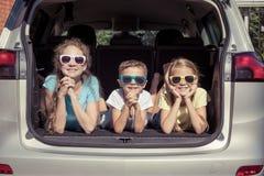 Il fratello felice e le sue due sorelle stanno sedendo nell'automobile al fotografia stock libera da diritti