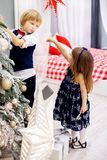 Il fratello piccolo e la sorella decora un albero di Natale nella stanza Immagine Stock Libera da Diritti