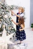 Il fratello piccolo e la sorella orna l'albero di Natale nella stanza Immagine Stock