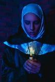 Il freddo tonifica il ritratto del monaco femminile con la candela in mani Immagini Stock
