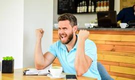 Il fronte aggressivo teso di espressione dell'uomo si siede il caffè con la tazza di caffè e del blocco note Emicrania e sforzo C fotografie stock
