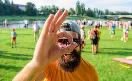 Il fronte allegro dell'uomo guarda con il gesto giusto Uomo barbuto davanti al fondo della riva del fiume della folla Sia sicuro  fotografia stock libera da diritti