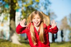 Il fronte allegro dello smorfia della ragazza in cappotto gode del parco di caduta Svago allegro del bambino Capelli lunghi biond fotografia stock libera da diritti