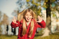 Il fronte allegro dello smorfia della ragazza in cappotto gode del parco di caduta Svago allegro del bambino Capelli lunghi biond fotografia stock