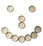 Il fronte con un sorriso dai coperchi della birra Immagini Stock Libere da Diritti