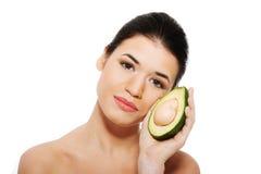 Il fronte della bella donna con l'avocado. fotografie stock