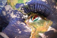 Il fronte della donna con struttura del pianeta Terra e bandiera delle Seychelles dentro l'occhio Fotografia Stock Libera da Diritti
