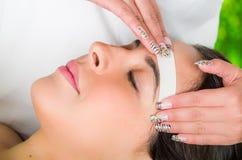 Il fronte della donna del primo piano che riceve trattamento della cera dei capelli facciali, bellezza e concetto di modo Fotografie Stock Libere da Diritti