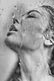 Il fronte della donna nel vetro bagnato Fotografie Stock Libere da Diritti