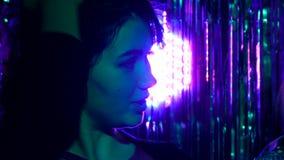 Il fronte della ragazza è evidenziato di un da un proiettore colorato multi video d archivio