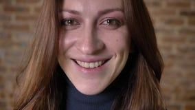 Il fronte della ragazza marrone dei capelli con gli occhi pieni degli strappi sta guardando alla macchina fotografica, fondo vago archivi video