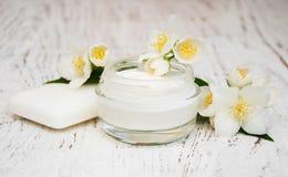 Il fronte e gli idratante della crema per il corpo con il gelsomino fiorisce su bianco Fotografia Stock Libera da Diritti