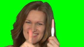 Il fronte felice della donna che mostrano il test di gravidanza positivo ed i pollici aumentano il gesto archivi video
