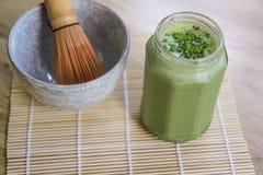 Il frullato del tè verde di Matcha in barattolo di vetro sulla stuoia di bambù con la ciotola di pietra e di legno sbattono Fotografia Stock Libera da Diritti