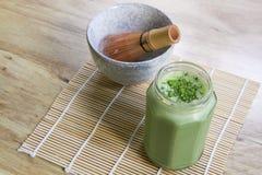 Il frullato del tè verde di Matcha in barattolo di vetro sulla stuoia di bambù con la ciotola di pietra e di legno sbattono Immagini Stock