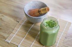 Il frullato del tè verde di Matcha in barattolo di vetro sulla tavola con la ciotola di pietra con di legno sbatte nel fondo Sopr Fotografie Stock Libere da Diritti