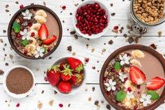 Il frullato della proteina della banana del cioccolato lancia con granola, la fragola ed il melograno decorati con i fiori Immagine Stock