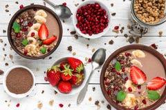 Il frullato della proteina del cacao o del cioccolato e della banana lancia con i semi del granola, della fragola e del melograno fotografia stock libera da diritti