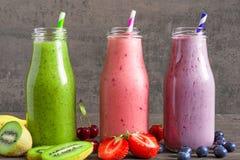 Il frullato variopinto beve in bottiglie con una paglia e una frutta fresca e le bacche Fotografie Stock