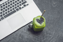 Il frullato verde fresco con la banana e gli spinaci con cuore dei semi di sesamo e di un computer portatile amano per un concett Immagine Stock Libera da Diritti