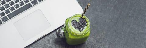 Il frullato verde fresco dell'INSEGNA con la banana e gli spinaci con cuore dei semi di sesamo e di un computer portatile amano p Fotografie Stock