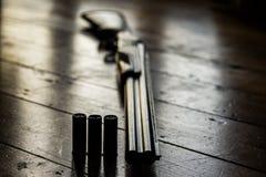Il fucile da caccia ha incaricato delle pallottole e delle pallottole di riserva sul pavimento di legno, Fotografie Stock