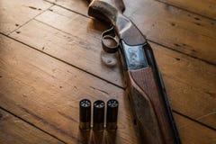 Il fucile da caccia ha incaricato delle pallottole e delle pallottole di riserva sul pavimento di legno, Immagini Stock