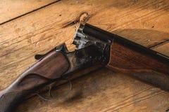 Il fucile da caccia ha incaricato delle pallottole e delle pallottole di riserva sul pavimento di legno, Fotografia Stock