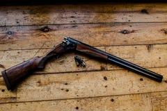 Il fucile da caccia ha incaricato delle pallottole e delle pallottole di riserva sul pavimento di legno, Immagini Stock Libere da Diritti