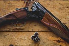 Il fucile da caccia ha incaricato delle pallottole e delle pallottole di riserva sul pavimento di legno, Fotografie Stock Libere da Diritti