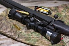 Il fucile nero con munizioni e portata sui precedenti del multicam Fine in su fotografia stock