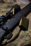 Il fucile nero con munizioni e portata sui precedenti del multicam Fine in su fotografie stock