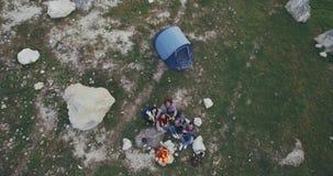 Il fuco che cattura il gruppo di amici alla natura che spendono il buon tempo al fuoco di accampamento che bevono e felici ha tem stock footage