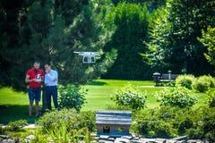 Il fuco compatto si libra davanti a due uomini dei pantaloni a vita bassa L'elicottero del quadrato vola vicino al pilota Innov d Fotografie Stock Libere da Diritti