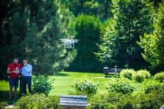 Il fuco compatto si libra davanti a due uomini dei pantaloni a vita bassa L'elicottero del quadrato vola vicino al pilota Innov d Fotografia Stock Libera da Diritti