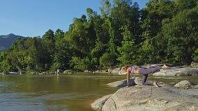 Il fuco gira intorno alla ragazza nella posa di yoga su Boulder liscio video d archivio