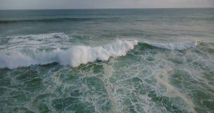 Il fuco inclina giù per seguire la grande onda di oceano blu che raggiunge la riva e che si schianta con seafoam bianco un giorno video d archivio