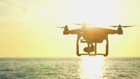 Il fuco nel cielo di tramonto le montagne dell'onda di oceano si chiudono su di quadrocopter all'aperto concetto per la videograf archivi video