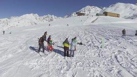 Il fuco pilota i cerchi sopra gli sciatori e gli snowboarders sulla collina innevata dell'inverno completano stock footage