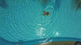 Il fuco si avvicina a a nuoto della ragazza in acqua d'increspatura dello stagno archivi video