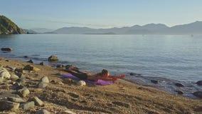 Il fuco si muove intorno alla ragazza nella posa di yoga contro l'oceano di mattina archivi video