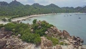 Il fuco si muove sopra la piccola penisola rocciosa verso la spiaggia di sabbia archivi video