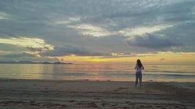 Il fuco si muove verso la ragazza che cammina vicino al mare contro l'alba dorata stock footage
